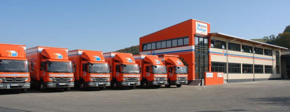 Auf einer Breitformat-Aufnahme sieht man links 6 kurze orangene LKW aufgereiht geparkt und in der rechten Bildhälfte das neue Verwaltungsgebäude der Spedition. Es ist blauer wolkenloser Himmel. Vorne ist viel Hoffläche.