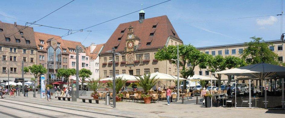 Man sieht das Rathaus von Heilbronn mit Marktplatz vor blauem Himmel ohne Wolken. Im Vordergrund sind die Gleise der Stadtbahn. Rechts ist ein Cafe mit ausgebreiteten Schirmen. In der Mitte liegt die Haltestelle.