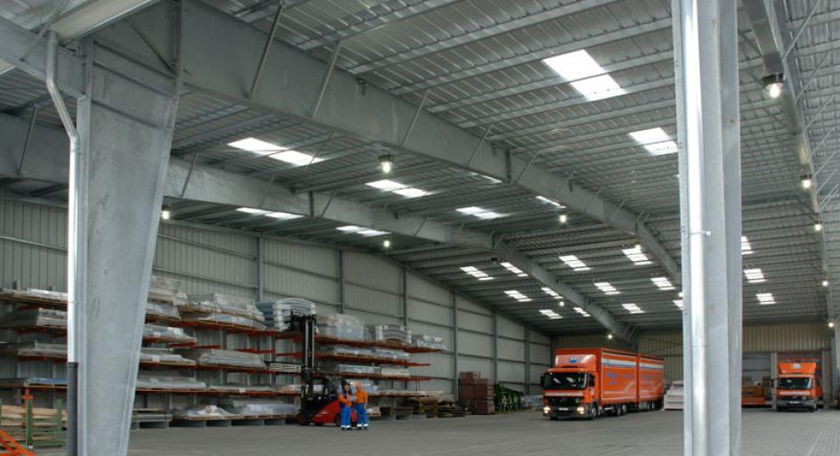 Lagerfläche in einer riesigen Lagerhalle, die von Dachfenster lichtfurchflutet ist. Man sieht vorne die Stahlträger und die Stahl-Querverstrebung. An der Seite lagert Langgut auf Regalen. Man sieht 2 orangene LKW, einer davon mit Anänger. Ebenfalls 2 Pers