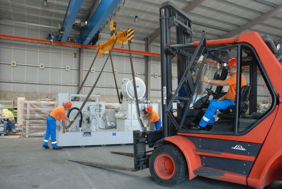 3 Mitarbeiter kümmern sich um eine große hellgraue Maschine, die am Kran - an der Decke - hochgehoben werden soll: 2 sind an der gauen Maschine, einer sitzt im Stapler.