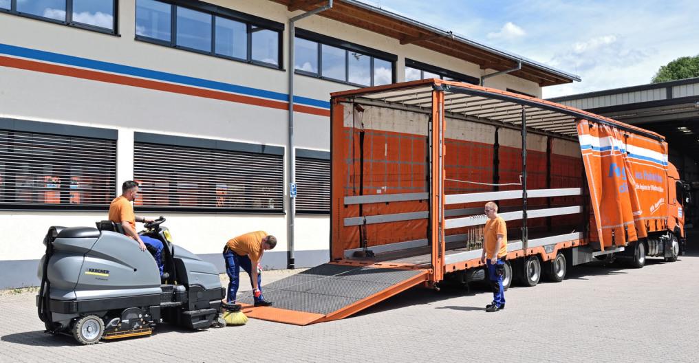 Ein LKW-Fahrer sther vor einem kurzen LKW und schaut auf sein elektronisches Gerät. Eine Hand ist am Türgriff. Im Bild ist ein kompletter und zwei hälftige orangenen LKW vor Laderampen.