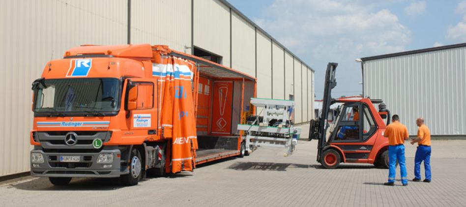 LKW-Fahrer und LAgerist stehen hinter dem Gabelstapler, der auf einer Palette eine sehr große Maschine in einen Planentieflader einlädt. Der LKW ist orange, das Wetter ist schön, der Himmel ist blau.