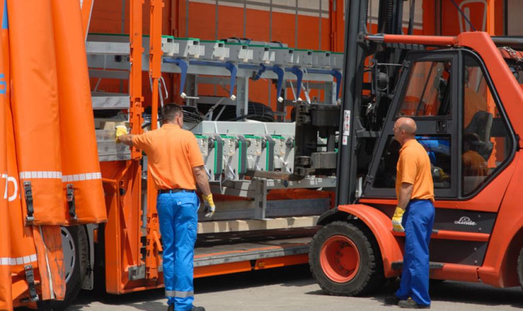 LKW-Fahrer und Disponent der Spedition in Hohenlohe, stehen vor Stapler mit Maschine, die bereits auf die Ladefläche des orangenen LKW geladen ist. Es ist ein Planentieflader.