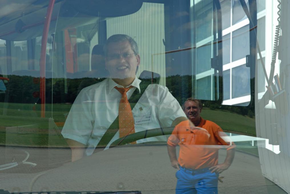 LKW-Fahrer und der Inhaber der Rüdinger-Spedition in Hohenlohe: man sieht den Firmenchef auf dem Fahrersitz eines Busses durch die Windschutzscheibe. Der LKW-Fahrer spiegelt sich im Glas.