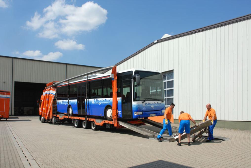 LKW-Fahrer und zwei Lager-Spezialisten entfernen die beiden Rampen, auf denen ein blauer Nahverkehr-Bus auf einen Planentieflader fuhr. Alles ist im freien, bestes Wetter, blauer Himmel, weiße Wolken.