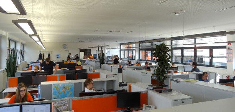 Es ist das Großraumbüro der Spedition Rüdinger, und zwar die Disposition. Die Trennwände sind in orange, man sieht von vielen Mitarbeitern gerade den Kopf oder den Oberkörper. Es ist ein heller Raum.