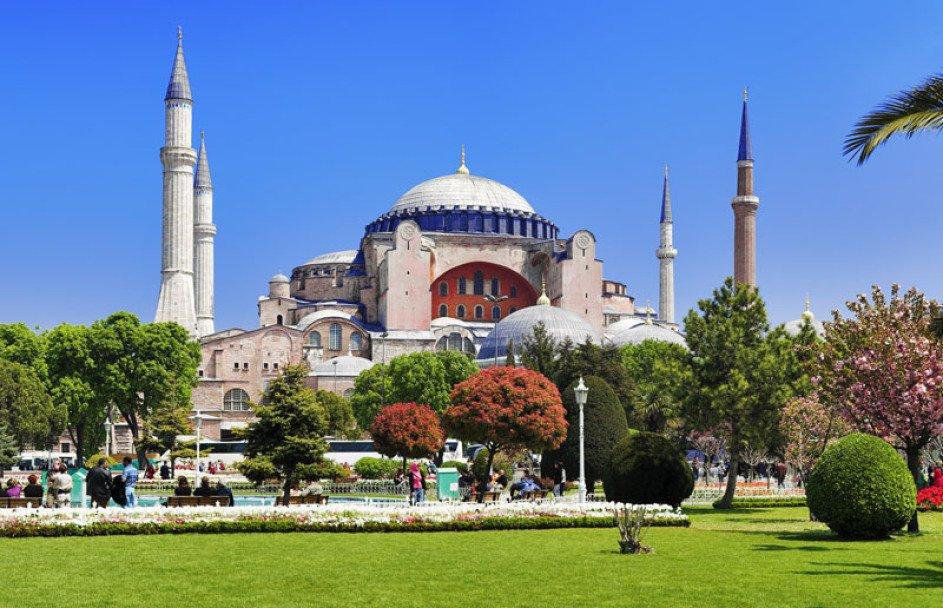 Man sieht auf die Hagia Sophia in Istanbul. Das Wetter ist perfekt, der Himmel blau. Man sieht 4 MInarette und in der Mitte eine Kuppe. Vorne ist ein hübscher Garten mit Büschen, Bäumen und Rasen.