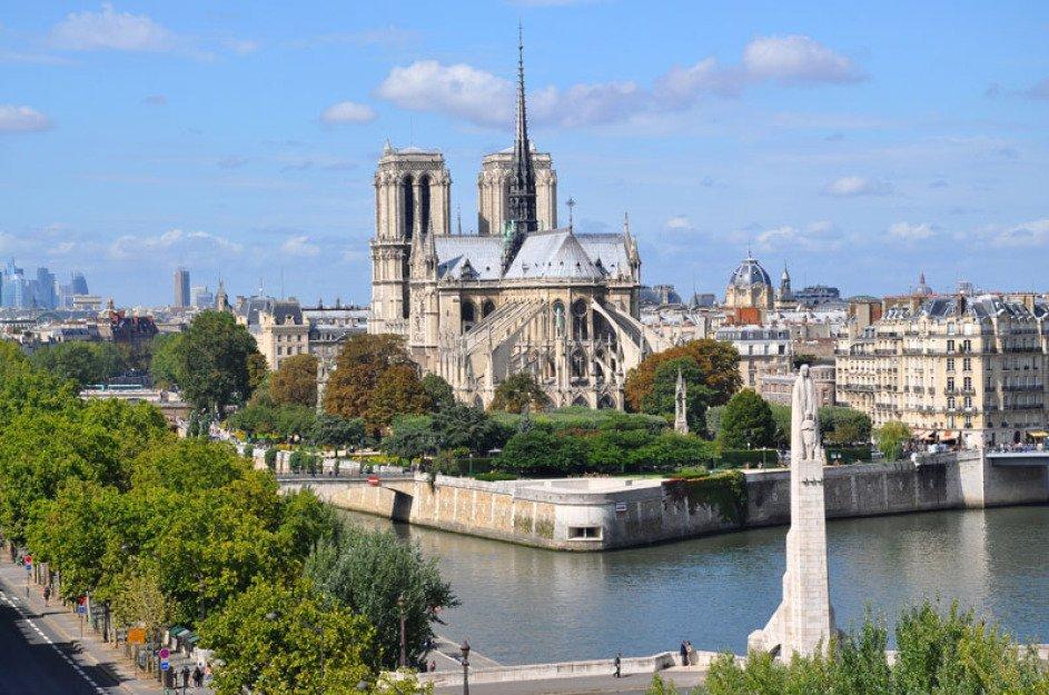 Man blickt über die Seine in Paris hinweg auf die Kirche Norte Dame. Man sieht sie von der Rückseite. Man sieht die Seine sich davor gabeln. Links sind hellgrüne Bäume, rechts Wohnhäuser.