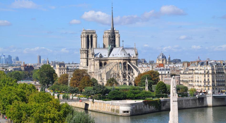 """Man sieht auf die Kirche Notre Dame in Paris und zwar von der Rückseite. Zu erkennen ist auch die Insel in der Seine, die zu beiden Seiten vorbei fließt. Links sind Bäume, im Hintergrund """"La Defense""""."""