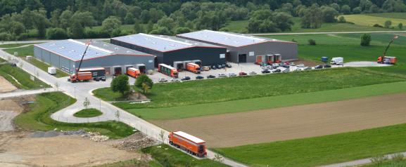 Es ist ein Foto von einem nahen Weinberg, fast eine Luftaufnahme. Zwischen Wald und Grünflächen rechts und unten sind drei Lagerhallen. Links ist eine Straße mit Wendeschleife. Mehrere orangen LKW sind sichtbar.