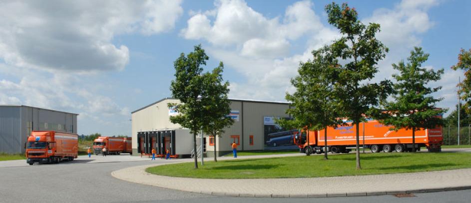 Lagerhallen bilden den Hintergrund des Motives. Davor sieht man 3 sehr lange organgene LKW und im Vordergrund ist ein Verkehrskreisel mit Bäumen und niedrigem Gras in der Mitte. Weiße Wolken sind am Himmel. Die Sonne scheint. Man erkennt 3 Mitarbeiter.