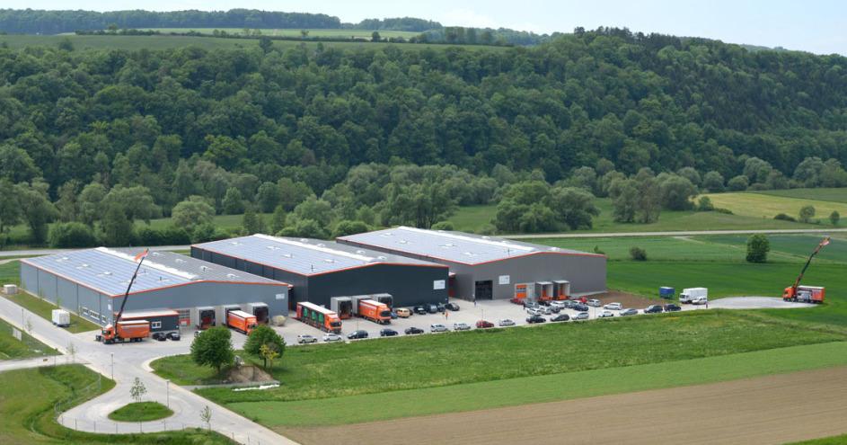3 Lagerhallen sind in der Mitte der linken Bildhälfte. Davor stehen viele Autos und mehrere orangene LKW. Die obere Hälfte des Bildes ist zu einem Viertel Himmel, zu drei Vierteln grüner Wald, das untere Viertel ist landwirtschaftliche Fläche.