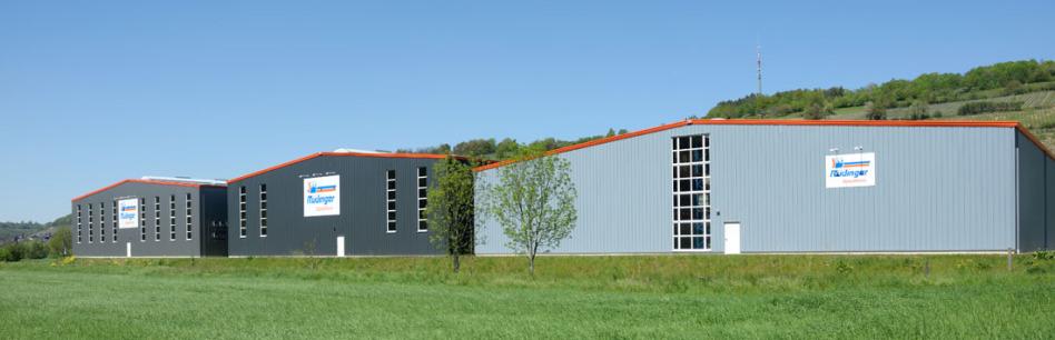 Man sieht auf 3 Lagerhallen in Dörzbach, im Main-Tauber-Kreis. Alle sind in verschiedenen Grautönen gehalten und haben Fenster mit weißen Rahmen. 3 Schilder sind angebracht. Im Vordergrund ist ein grünes Feld.