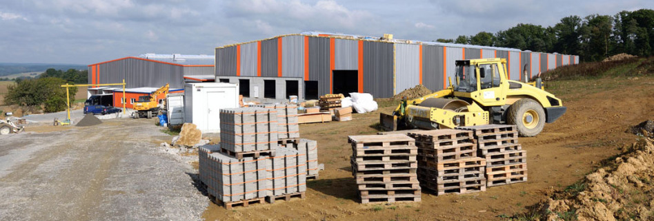 Eine Lagerhalle in Osterburken im Neckar-Odenwald-Kreis entsteht: Hinten sieht man 2 fast fertige Lagerhallen, vorne sieht man rechts leere Paletten, links Paletten mit Baumaterial. Dahinter steht ein Bagger.