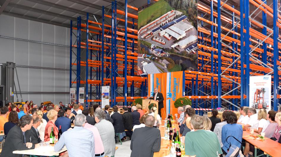 Eine Einweihungsveranstaltung. Am Rednerpult steht Roland Rüdinger, davor und von der Rückseite fotografiert sitzen viele Menschen an Bänken. Auffallend sind die orange/blauen noch leeren Regale mit einem Banner davor.