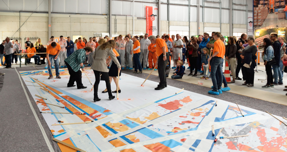 Viele Menschen stehen rund um eine weiße schon teilweise bemalte Plane, noch viel mehr stehen umher. Auf der Plane sieht man die Menschen mit langen Pinseln malen.