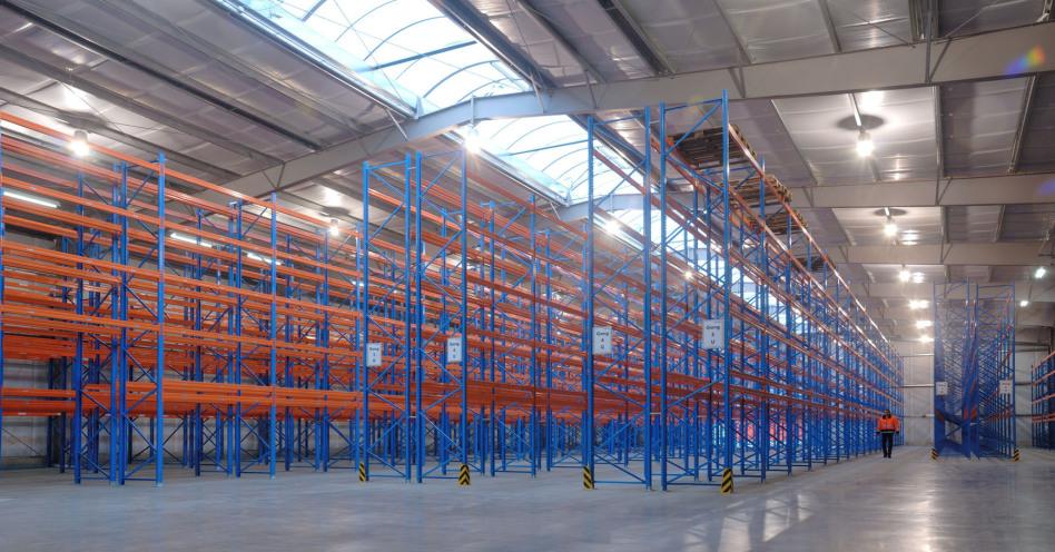 Eine beeindruckende Aufnahme einer leeren Halle im Paletten-Lager der Spedition Rüdinger. Noch komplette ohne Waren ist es eine Collage aus orange/blauen Regalen und Metall an der Decke.