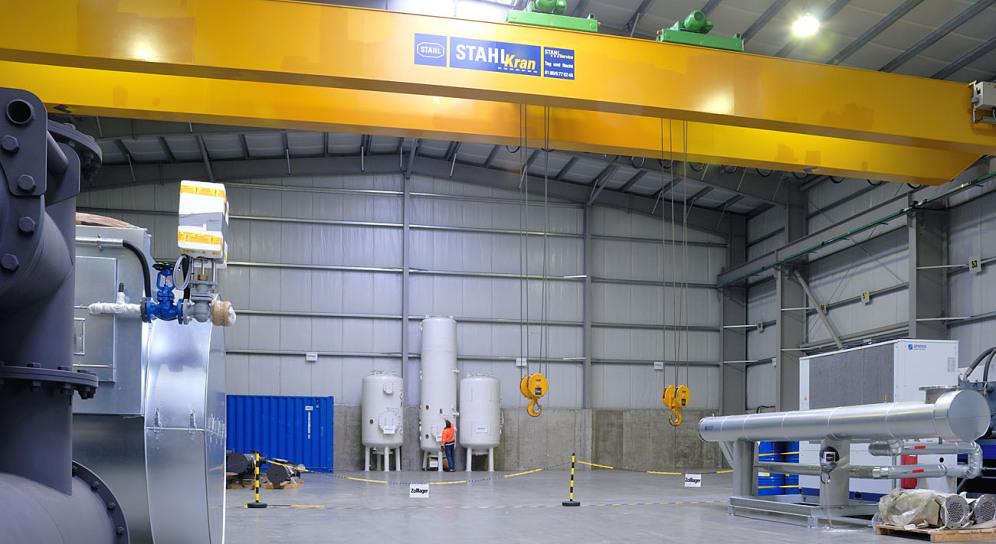 Unter einem gelben 32-Tonnen-Kran im Kranlager der Spedition sieht man das durch eine Kette abgetrennte Zolllager: 2 Haken hängen von oben herab und ein Mitarbeiter verdeutlicht das Größenverhältnis.