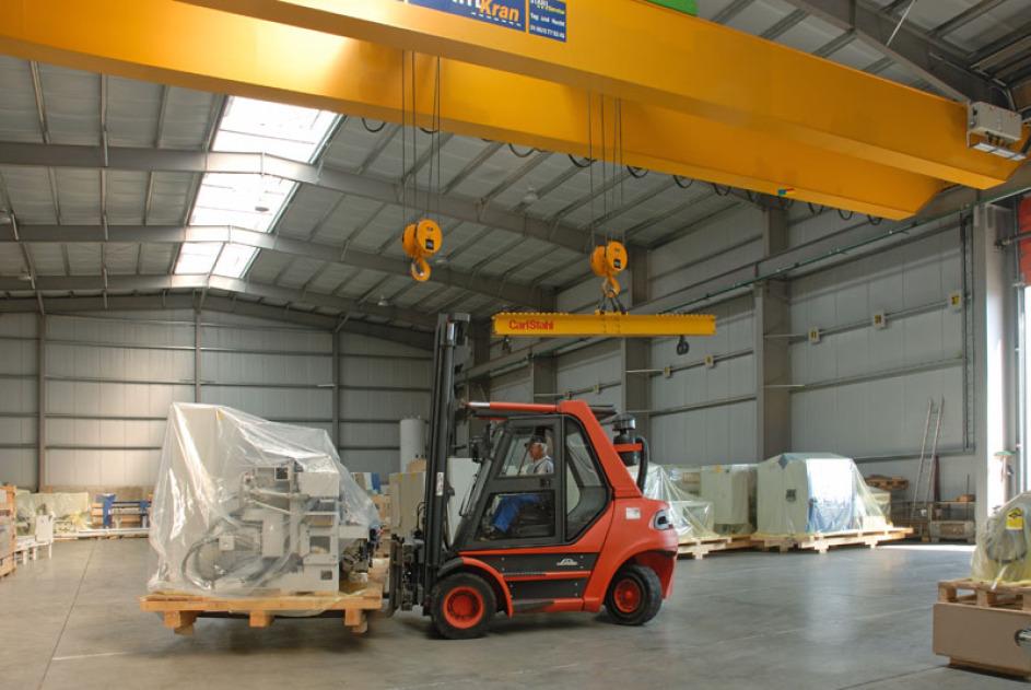 Ein roter Gabelstapler in der Mitte des Bildes transportiert eine in eine Folie verpackte kleinere Maschine. Über ihm sieht man den gelben 32-Tonnen-Kran, an dem zwei Haken hängen.