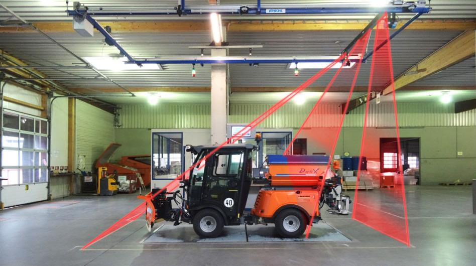 Eine Kehrmaschine steht in einer Lagerhalle auf einer Bodenplatte. Man sieht ein APACHE-Vermessungsgerät, symbolisiert durch 3 Laserfeld-Bereiche in rot. Das Gerät ist an mehreren blauen Schienen installiert.