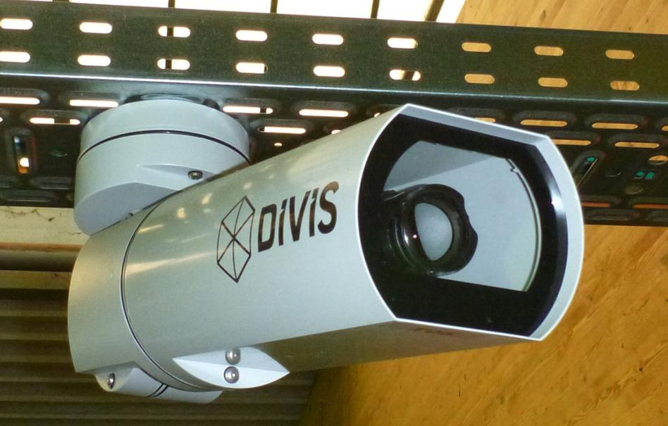 Das Bild ist komplett mit einer Kamera des DIVIS-Systems ausgefüllt, die an einer Stahlschiene befestigt ist. Man sieht von unten auf die Optik vorne.