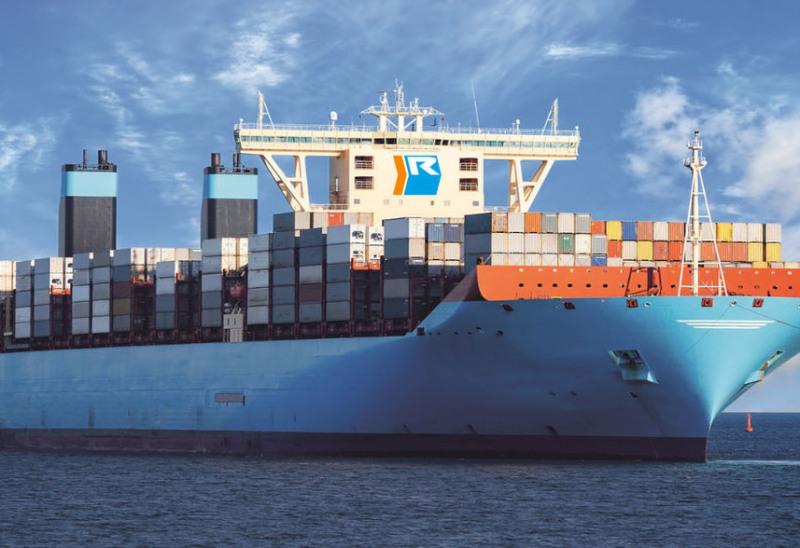 Man sieht den Hamburger Hafen, rechts und links sind Kräne. rechts auch ein Containerschiff. Im Hintergrund links geht gerade die Sonne auf.