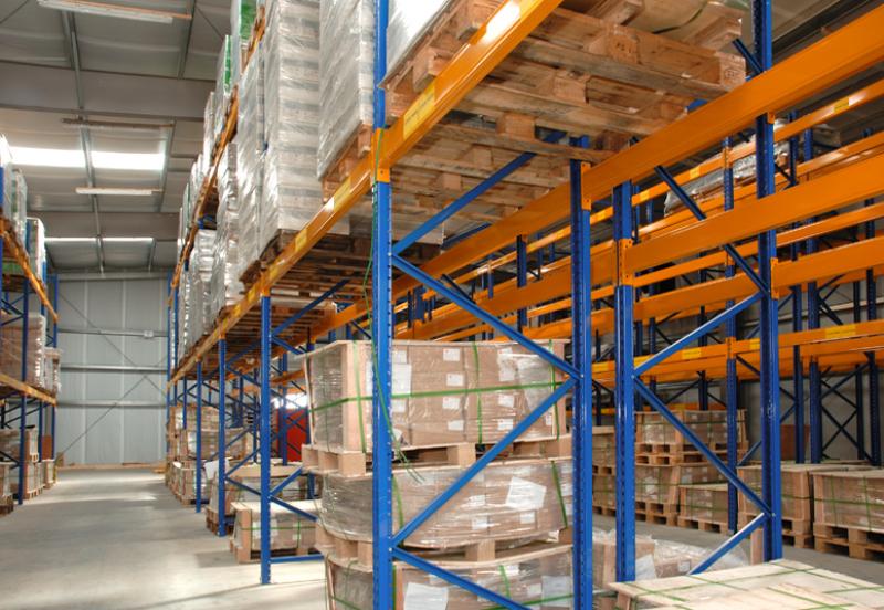 Man sieht in eine der Regalreihen der Spedition, in der im zweiten Stock auch Waren eingelagert sind. Die Stahlrahmen sind orange, die Querleisten sind gelb.