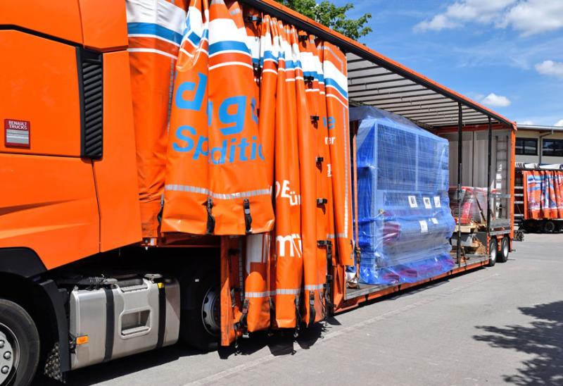 In einem Gelände zwischen mehreren Lagerhallen wird ein Bus auf einen großen Speditions-Lkw verladen. Drei Mitarbeiter arbeiten am hinteren Ende des Lkws an der Rampe, der Bus steht bereits auf dem Fahrzeug.