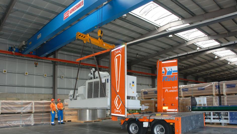 In einer Halle der Spedition haben zwei Mitarbeiter eine Maschine an einem 38-Tonnen-Kran hängen. In der rechten Bildhälfte sieht man den hinteren Teil des Hängers eines offenen Planentiefladers.