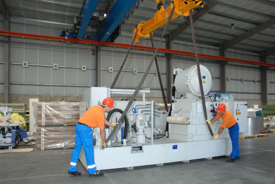 Ein graue Maschine wird unverpackt von zwei Mitarbeitern in der Spedition an eine 38-Tonnen-Kran gehängt. Die Mitarbeiter haben blau/orangene Kleidung an und tragen beide einen Helm.