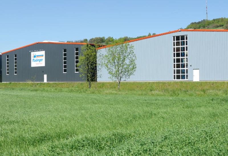 Man sieht 2 Lagerhallen in grauer Farbe, eine mit dem Schild der Rüdinger-Spedition. Vorne ist der Vordergrund – die komplette untere Bildhälfte – satt grün bewachsen, oben ist der Himmel hellblau.