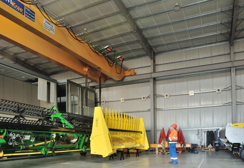 In einem der Lager der Spedition sieht man an der Decke einen 38-Tonnen-Kran in gelber Farbe. Darunter steht eine landwirtschaftliche Maschine in grün und gelb. Davor steht ein Mitarbeiter mit einem Helm.