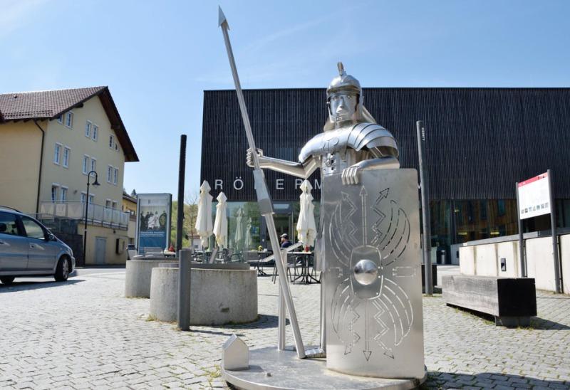 In der rechten Bildhälfte ist die Nachbildung eines Römers in Rüstung. Er steht mit Lanze und Schild vor dem Museum in Osterburken im Neckar-Odenwald-Kreis. Links ist ein Wohnhaus und davor parkt ein Pklw.
