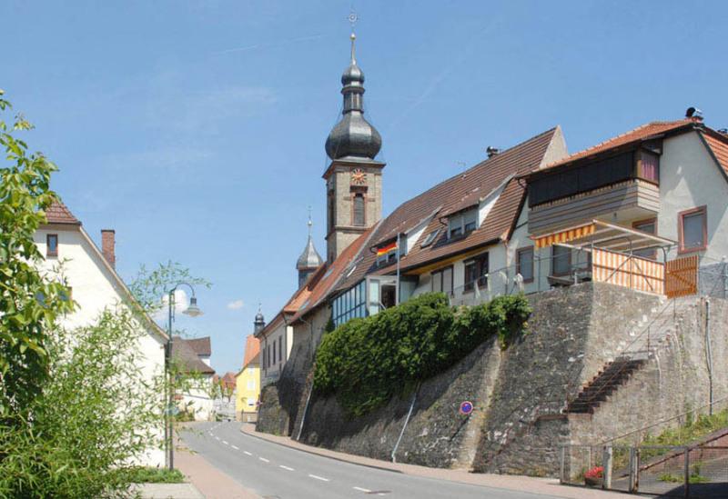 Man sieht eine Straße innerorts in Boxberg im Main-Tauber-Kreis. Sie führt von der Bildmitte nach oben. Auf der rechten Seite steht eine Kirche hinter 2 Wohnhäuser, Der Himmel ist blau und wolkenlos.