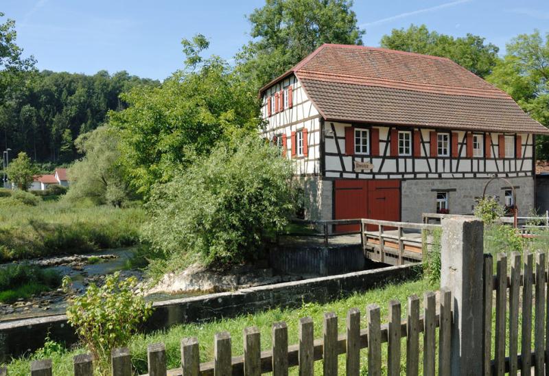 Man sieht eine schöne Mühle, ein Fachwerkhaus in Dörzbach, im Kreis Hohenlohe, davor ist eine Wiese und davor ein Gartenzaun. Rundherum sind Bäume, der Himmel ist blau, die Sonne scheint.