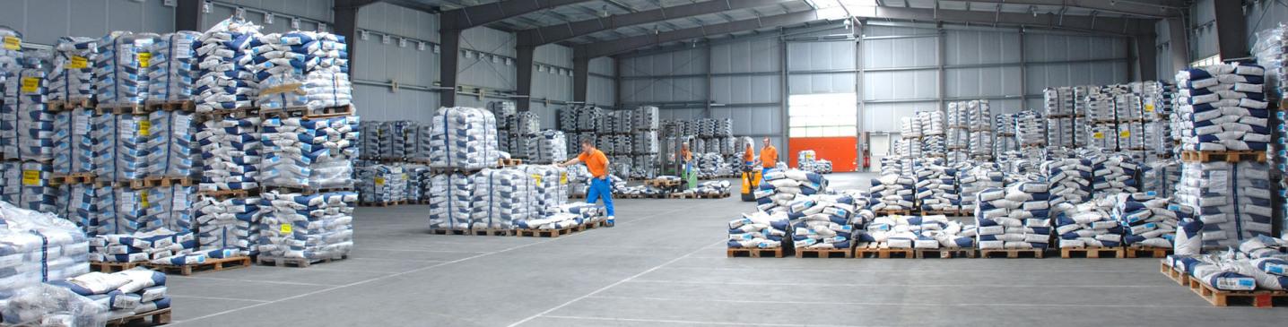 Ein extremes Breitformat-Foto: Es ist eines der Blocklager von innen, eine riesige plane Lagerfläche. In verschiedenen Sektionen sind blau-weiße Säcke auf Paletten abgestellt. 3 Mitarbeiter, orange-blaue Kleidung, arbeiten.