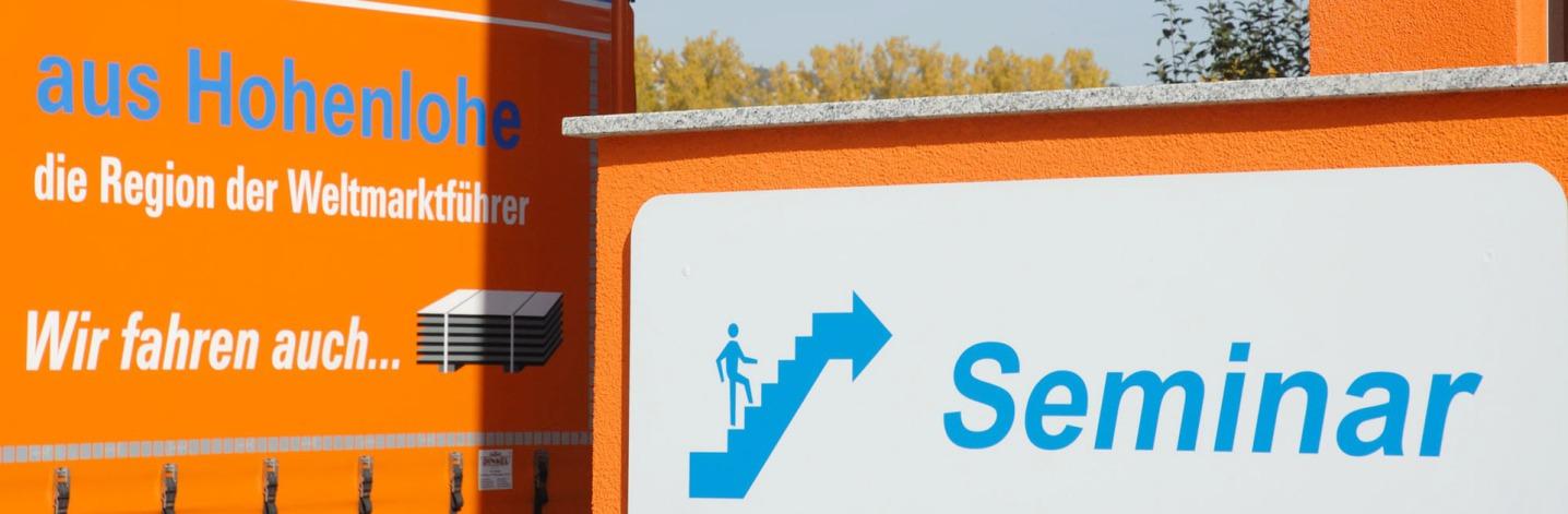 """In der linken Hälfte des Bildes ist die Plane eines Lkw: """"aus Hohenlohe, die Region der Weltmarktführer"""" steht darauf. Rechts ist ein gewaltig groß fotografiertes Schild: Seminar und ein Piktogramm """"Treppe""""."""
