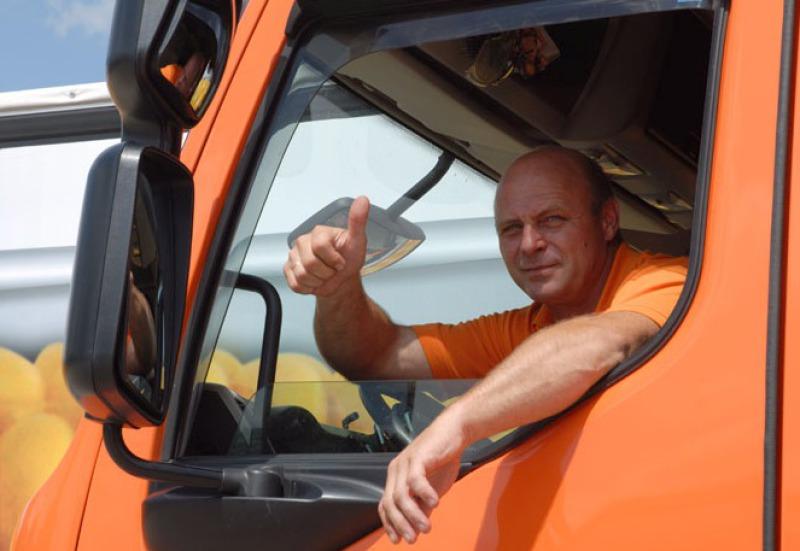 """In der Fahrerkabine eines orangenen Lkws sitz der Fahrer und schaut zum Seitenfenster hinaus. Zum Fotografen macht er das Zeichen """"Daumen hoch"""" und lächelt."""