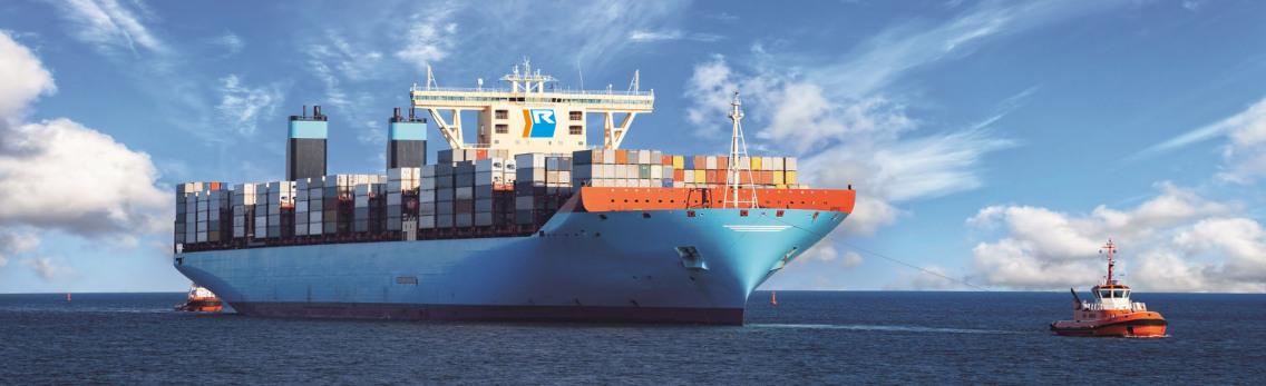 Sonnenuntergang im Hamburger Hafen, links sieht man die fast untergehende Sonne. Rechts und links sind Verladekräne, rechts sind zwei Schiffe für den Container-Transport. Der Himmel ist wolkenlos, das Wasser ruhig.