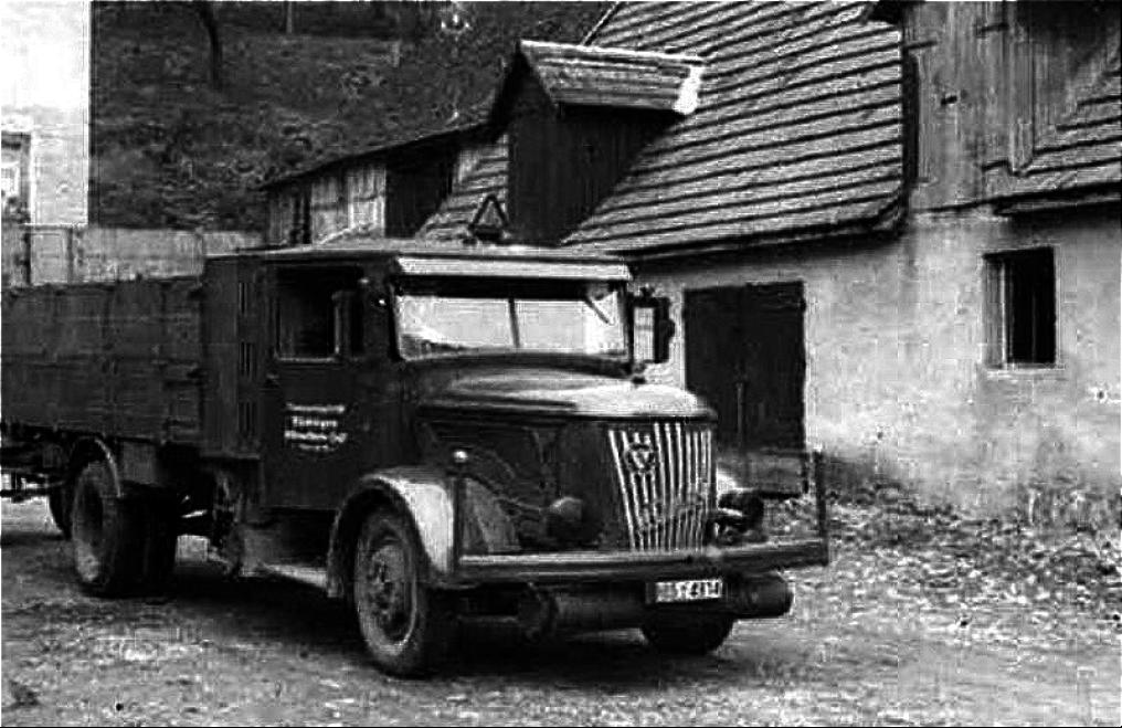 Schwatzweiß ist ein historisch-uralter Lkw dargestellt, der vor einem historischen Haus parkt. Er hat eine offene Ladefläche. Das Bild ist so unscharf, dass man die Autonummer nicht erkennt.