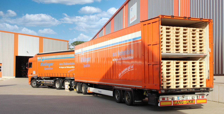 Ein fast beladener Doppelstock-Transport-Anhänger hinter einen Zugmaschine. Das Bild ist von schräg oben fotografiert. Rechts sieht man einen Gabelstapler und einen Mitarbeiter. Deutlich sieht man 2 Ladeflächen übereinander.