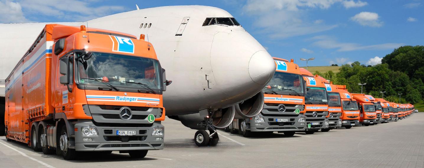 Auf einer Fotomontage sieht man eine lange Reihe von 40-Tonnen-Lkw. Der zweite Lkw in dieser Reihe ist entfernt und stattdessen ein weißes riesiges Flugzeug, eine Boeing 747, einmontiert.