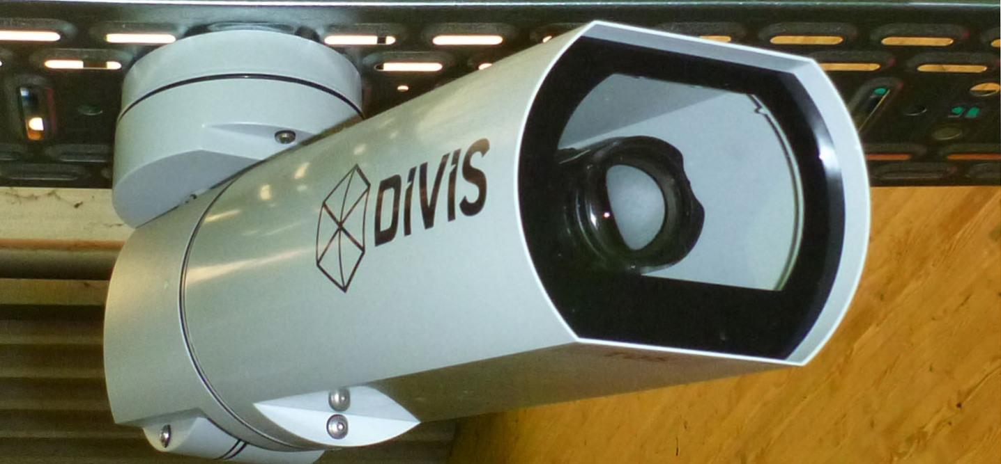 """Thema Videoüberwachung: eine riesig fotografierte bildfüllende Videokamera mit der Aufschrift """"DIVIS"""" ist schräg von vorne aufgenommen. Man sieht die Linse hinter der Frontscheibe."""