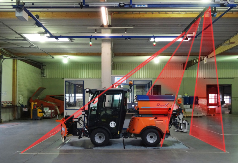 Eine Kehrmaschine steht auf einer Abmessungsebene auf dem Boden. Von der Decke symbolisieren 3 Laserstrahlbereiche und Laserillustrationen die Vermessung diese Kehrmaschine.