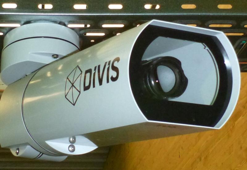 """Man sieht eine riesige Videokamera, von leicht unten fotografiert, mit der Aufschrift 2DIVIS"""":"""