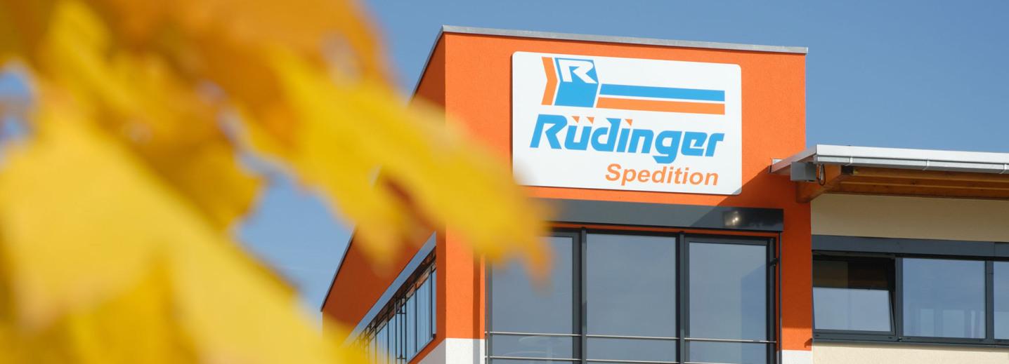"""Es ist die obere Ecke des neuen, modernen Verwaltungsgebäudes der Spedition Rüdinger. Besonders groß ist das Schild """"Rüdinger Spedition"""" fotografiert. Links sind riesige gelbe Blätter unscharf im Vordergrund."""