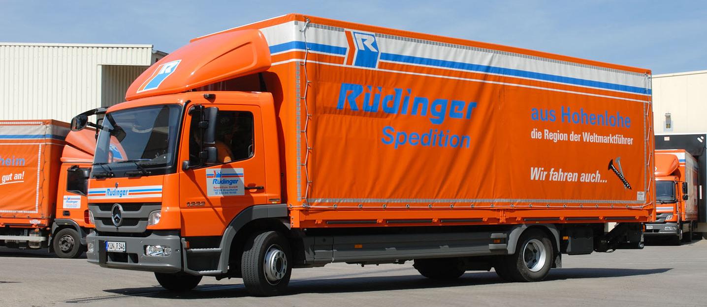 """12-Tonnen-Lkw steht diagonal vor weiteren Lkw der Spedition, die man aber nur wenig sieht. Auf seiner Plane liest man: """"Rüdinger Spedition aus Hohenlohe – die Region der Weltmarktführer""""."""