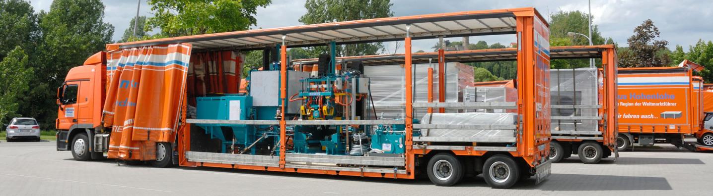 Ein XXL-Planentieflader, ein Jumbo-Lastzug. Er steht diagonal im Bild vor zwei weiteren XXL-Transportern. Er hat eine Maschine geladen, unverpackt. Die komplette Plane ist aufgeschoben.