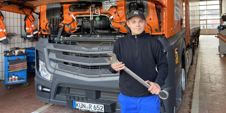 Ein Mitarbeiter kniet, ein Mitarbeiter beugt sich vor und beide schauen in den Motor eines Lkw. Dazu ist die Motorhaube offen und die Fahrerkabine ist nach vorne gekippt. Das passiert in der Werkstatt.