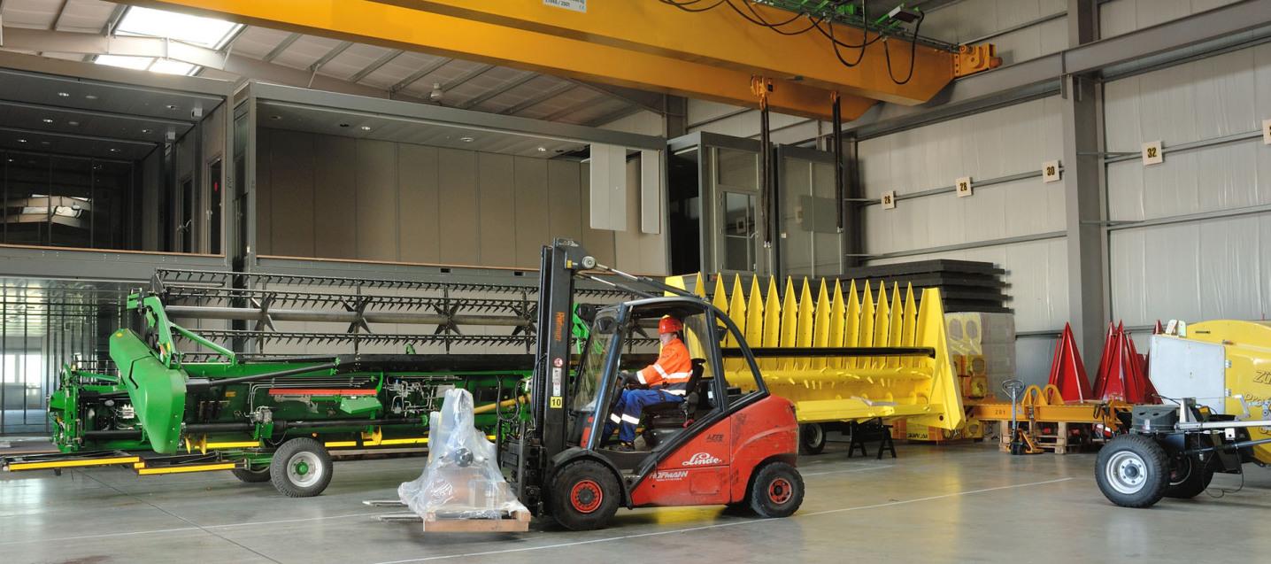 Man sieht das Innere einer Lagerhalle. Oben kann man den gelben 32-Tonnen-Kran erkennen, unten stehen zwei sehr große Maschinen. Bildmittig fährt ein Gabelstapler mit einer kleinen Palette.